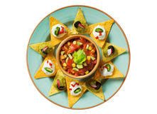 Nachos with dips and a bowl of salsa. Tortilla chips arranged around a bowl of salsa royalty free stock images