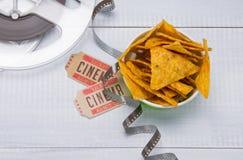 Nachos in einem Eimer, zwei Karten für Filme und Film, auf einem hellgrauen Hintergrund, Nahaufnahme lizenzfreie stockfotos