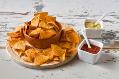 Nachos en un cuenco y salsas de la loza de barro Imagen de archivo libre de regalías