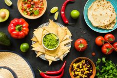 Nachos with guacamole, beans, salsa and tortillas. Mexican food. Table top view stock photography
