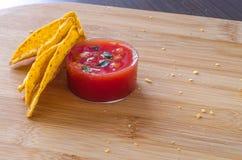 Nachos med kryddig salsa doppar och spridde runt om smulor royaltyfri bild