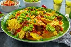 Nachos med ost, jalapenopeppar, den röda löken, persilja, tomaten, salsa, guacamolesås och tequila på den gröna plattan Royaltyfria Bilder