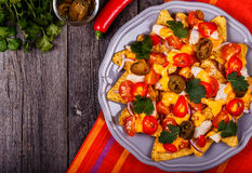 Nachos with melted cheese sauce, jalapeno, chicken and vegetable Royalty Free Stock Images