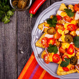 Nachos with melted cheese sauce, jalapeno, chicken and vegetable Stock Images