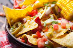 Nachos with melted cheese sauce, salsa and corn cobs in bowl on brown wooden background stock image