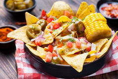 Nachos with melted cheese sauce, salsa, corn cobs Royalty Free Stock Images