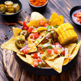 Nachos with melted cheese sauce, salsa, corn cobs Royalty Free Stock Photography