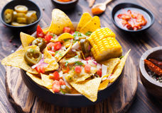Nachos with melted cheese sauce, salsa, corn cobs Stock Photos