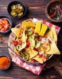 Nachos with melted cheese sauce, salsa and corn cobs in bowl on wooden background Top view Stock Images