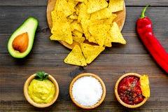Nachos mexicains populaires de casse-croûte Tortilla de nacho de Tiangle près de sause de Salsa et de guacamole, poivre de piment photographie stock libre de droits