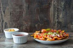 Nachos mexicanos con carne de vaca, guacamole, salsa de queso, pimientas, el tomate y la cebolla en placa en la madera Imagen de archivo libre de regalías