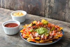 Nachos mexicanos con carne de vaca, guacamole, salsa de queso, pimientas, el tomate y la cebolla en placa en la madera Fotos de archivo libres de regalías