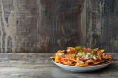 Nachos mexicanos con carne de vaca, guacamole, salsa de queso, pimientas, el tomate y la cebolla en placa en la tabla de madera Fotografía de archivo libre de regalías
