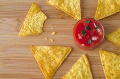 Nachos mexicanos das microplaquetas de milho ao redor do mergulho picante vermelho Foto de Stock