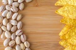 Nachos mexicanos das microplaquetas de milho com queijo e porcas de pistaches em shell rachados e inteiros Fotografia de Stock