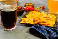 Nachos mit Tortilla-Chip-Tomatensalsa, Bohne und Senf und zwei Glas mit Bier auf rustikalem Steinhintergrund Ein Beschaffenheit b Lizenzfreies Stockbild