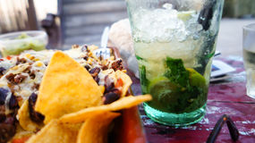 Nachos and mojito. Delicious nachos with cheese and minced meat with a fresh mojito Royalty Free Stock Images