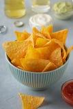 Nachos o tortilla de los bocados del maíz en cuenco azul con las salsas y la cerveza de inmersión en una tabla Foto de archivo