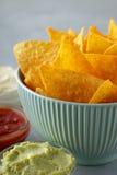 Nachos o tortilla en cuenco azul con las salsas de inmersión en la tabla gris Fotos de archivo libres de regalías