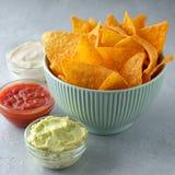 Nachos o tortilla mexicanos curruscantes de los bocados en cuenco con las salsas de inmersión en la tabla gris Fotos de archivo libres de regalías