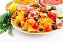 Nachos, olives, pork loin and vegetables Stock Photos