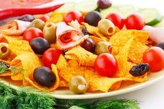 Nachos, olives, pork loin and vegetables Stock Image
