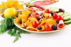 Nachos, olives, pork loin and vegetables Royalty Free Stock Photos