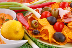 Nachos, olives, pork loin and vegetables Stock Images