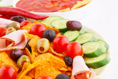Nachos, olives, pork loin and vegetables Royalty Free Stock Images