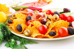Nachos, olives, pork loin and vegetables Stock Photography