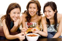Nachos and Salsa #2. Three pretty asian women eating nachos and salsa dip Royalty Free Stock Images