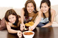 Nachos and Salsa #3. Three attractive asian women eating chips on the sofa Royalty Free Stock Photography