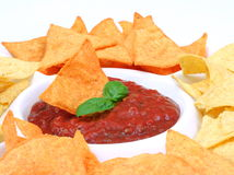 Nachos and salsa. Dip in a bowl and basil royalty free stock photo