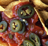 Nachos with salsa. Chips and jalapeno peppers royalty free stock photography