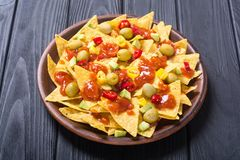 Nachos with sauce salsa. Traditional mexican food . Nachos with sauce salsa , olives , chili peppers and avocado royalty free stock images