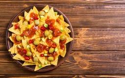 Nachos with sauce salsa. Traditional mexican food . Nachos with sauce salsa , olives , chili peppers and avocado stock photos