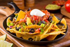 Nachos Supreme. A plate of delicious tortilla nachos with melted cheese sauce, ground beef, jalapeno peppers, red onion, green onions, tomato, black olives Stock Photos