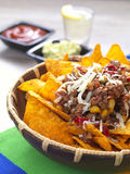 Nachos and tequila. A bowl with spicy tortilla chips served with minced meat and cheese stock image