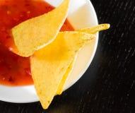 Nachos torrados deliciosos do milho com molho de tomate quente picante como um petisco ou um aperitivo em um disco branco Fotografia de Stock Royalty Free