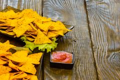 Nachos with Tortilla chips tomato salsa and mustard on rustic wooden background. A texture background.Copy paste place Royalty Free Stock Image
