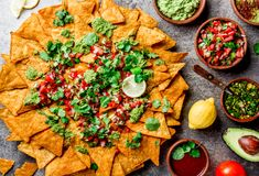 Nachos Totopos met sausen Mexicaans voedselconcept De gele spaanders van graantotopos met verschillende sausensalsas - pico del stock foto's