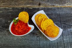 NachosCorn chipe mit adjika würziger Soße auf dem Tisch Lizenzfreie Stockfotos