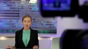 Nachrichten-Studio Junge und schöne Mädchenlesenachrichten im Fernsehen stock video
