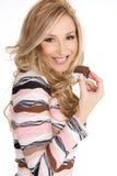 Nachsicht. Frau, die eine dekadente Schokoladentrüffel anhält Stockbild