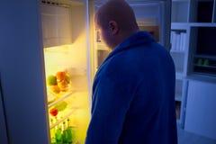 Am Nachtüberladenen Kerl öffnen Sie Kühlschrank Stockbild