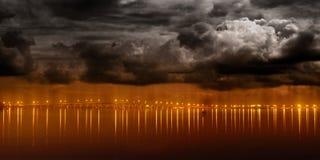 Nacht beleuchtet von der modernen Stadt, die über Wasser nachdenkt Lizenzfreie Stockfotos