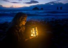 Nacht bij het strand, blondevrouw met lantaarn, golven van het overzees en wilde rotsvormingen op de achtergrond Stock Fotografie