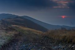 Nacht in de bergen Zonsondergang De hemel is de kleur van bloed openlucht Royalty-vrije Stock Afbeeldingen