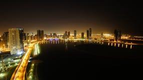 Nacht die van de stad van Sharjah op een meer wordt gezien Royalty-vrije Stock Afbeeldingen