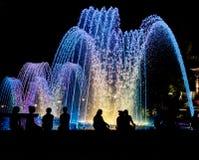 Nacht farbiger Brunnen mit Schattenbildern von Leuten Stockfotografie